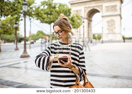 Lifestyle portrait of a young stylish business woman watching a time near the famous triumphal arch in Paris
