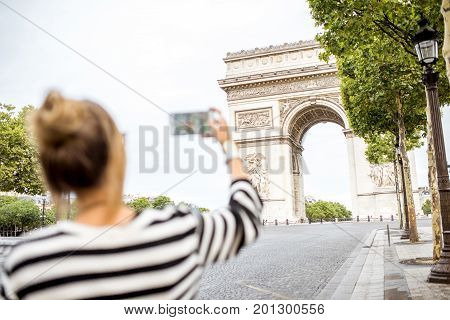 Young woman tourist photographing with phone famous triumphal arch in Paris. Image focused on the background, woman is out of focus