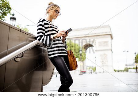 Lifestyle portrait of a young stylish business woman standing with phone near the famous triumphal arch in Paris