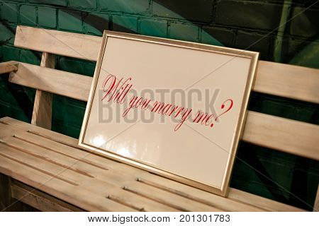 Label with frame and inscription will you marry me on wooden bench. Close up.