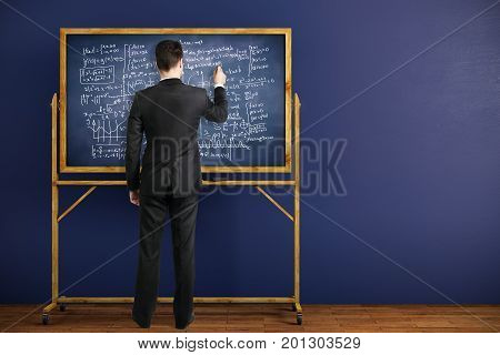 Back view of businessman writing mathematical formulas on chalkboard placed in interior with blue wall and wooden floor. Education concept. 3D Rendering