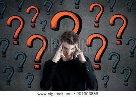 Pensive young caucasian man standing on concrete wall background with question marks. Curious confusion faq concept