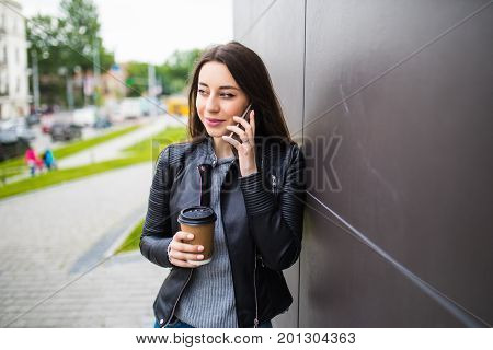 Beautiful Student Girl Leaning On Wall, Talking On Smart Phone And Holding Takeaway Coffee In Paperc
