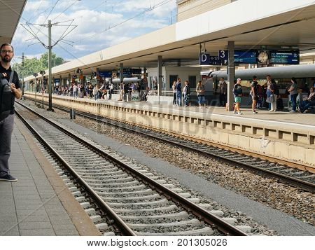 MANNHEIM GERMANY - AUG 8 2017: Large group of people waiting at the train station platform in Mannheim hauptbahnhof Train station commuting in German waiting for the delayed train