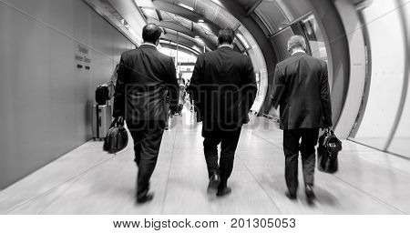 Unrecognizable black and white rear view of three executive businessmen walking toward the end of the international airport terminal to take the plane for the upcoming business meeting