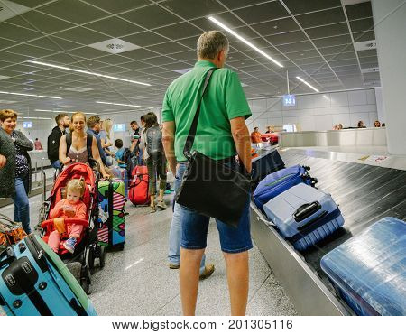 FRANKFURT GERMANY - AUG 8 2017: Passengers commuters waiting to claim the baggage luggage at modern airport looking at the luggage conveyor belt for their suitcase bag backpack