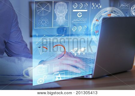 Side view of businessman hands using laptop with business screen hologram placed on office desktop with coffee cup. Finance concept. Double exposure