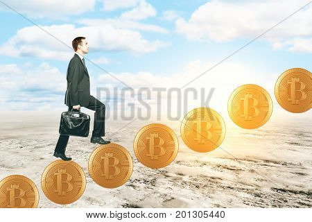Side view of young businessman climbing abstract bitcoin ladder on desert background. E-commerce concept. 3D Rendering