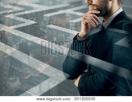 Thoughtful young businessman on abstract city background with maze labyrinth. Solution concept. Double exposure