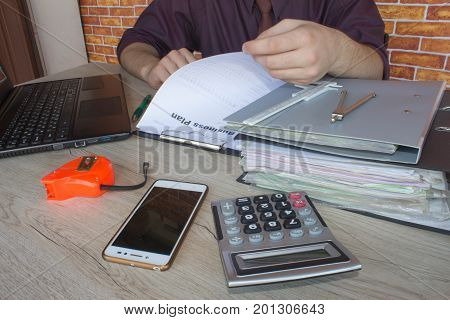 The calculators business owners accounting and technology business computer laptop calculator and documents in the office. Man doing his accounting financial adviser working