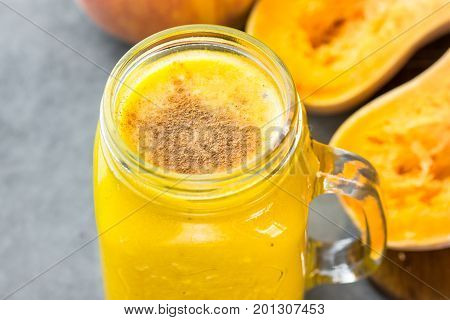 Glass mason jar with raw pumpkin butternut squash smoothie with peaches bananas cinnamon spices. Ingredients on dark stone table. Bight colors close up.