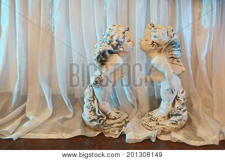 Original statuettes in the form of angels from stucco on a wedding day