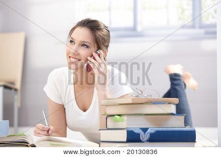 Attraktive College Girl im Chat auf Handy, Lächeln, Handauflegen Boden.?