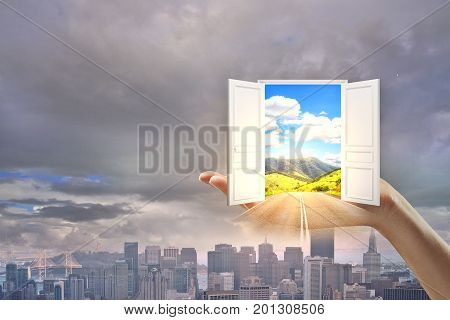 Hand holding abstract open door with bright landscape view on dull city background. Success and opportunity concept