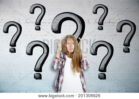 Worried young european woman on brick wall background with drawn question marks. Stress concept