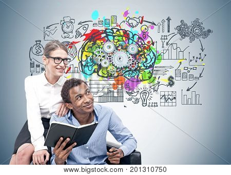 Smiling African American businessman and his blonde colleague in glasses sitting in an armchair near a gray wall with a colorful brain sketch and gears on it