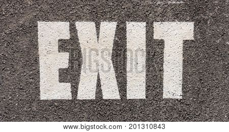 close up of white traffic exit sign on asphalt in a parking area in the city for traffic rule
