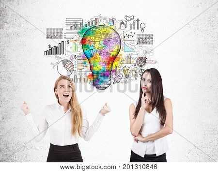 Happy blonde businesswoman screaming with joy and her pensive colleague standing near a concrete wall with a business idea sketch