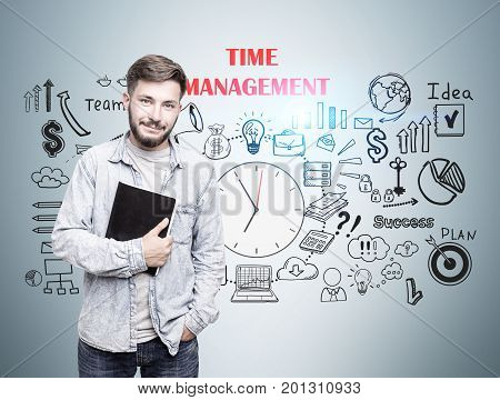 Portrait of a cheerful young man with a copybook standing near a gray wall with a time management scheme. Toned image
