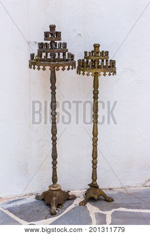close up of two old metal christian religious candle holders standing on a white wall