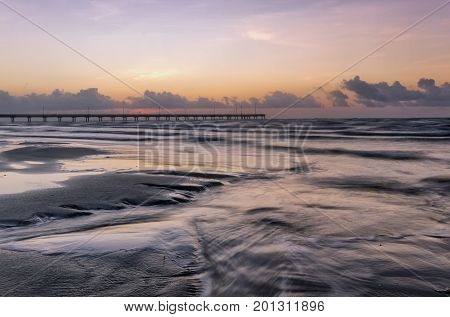 Horace Caldwell Fishing pier at sunrise with a long exposure on the crashing waves in the foreground located on Mustang Island in Port Aransas Texas
