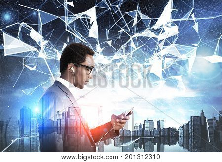 Side view of an African American man with a smartphone standing against a night city panorama. Polygons. Mock up toned image double exposure