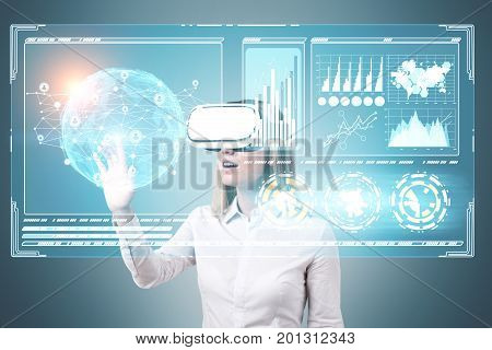 Blonde businesswoman wearing a white blouse and VR glasses is interacting with an Earth hologram and HUD. Toned image double exposure.