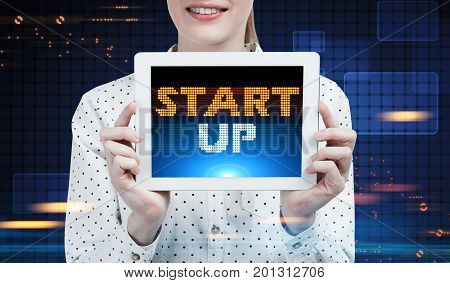 Close up of a businesswoman wearing a polka shirt holding a tablet computer and showing it to the viewer. There is a pixelated start up text. Dark blue futuristic background HUD. Toned image