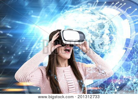 Young woman wearing a cardigan and VR glasses. She is amazed by what she is seeing. She is standing against an HUD Earth. Toned image double exposure
