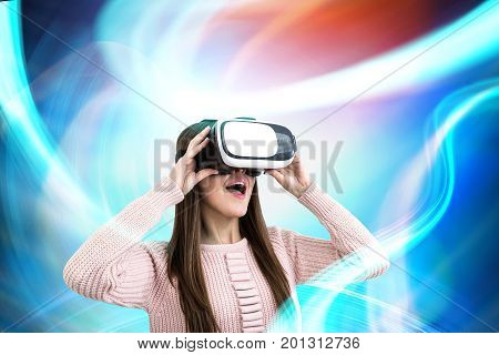 Close up portrait of a young woman wearing a pink cardigan and VR glasses. She is amazed by what she is seeing. She is standing against an abstract background. Toned image double exposure