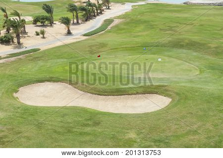 Aerial view over a tropical golf course with practice green and bunker sand trap next to fairway
