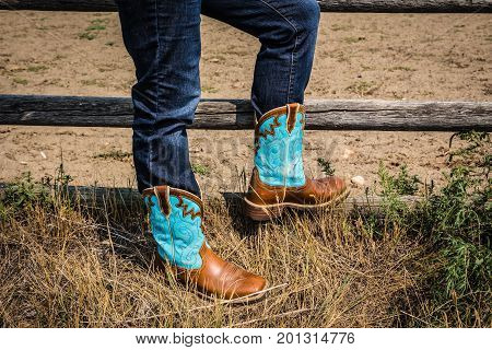 close up horizontal image of the bottom torso of a lady in jeans wearing a pair of ladies cowgirl boots in brown and teal blue leather.