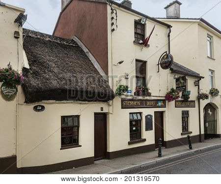 Galway Ireland - August 3 2017: The Hole in the Wall Bar shows yellow facade of old house with port and straw roof.
