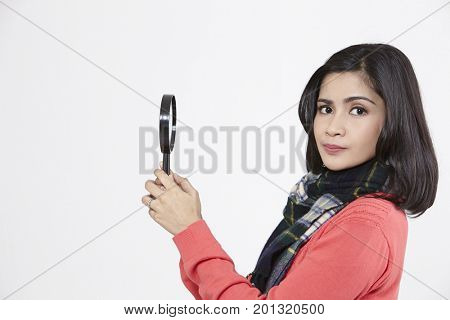 asian woman holding a magnifying glass on the white background