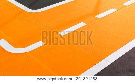 Curve of orange running track and lanes. Temporary setup detail on carpet floor.