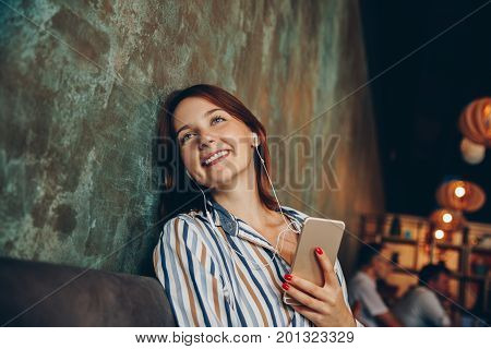 Young woman listen music with headphones and relaxing. Sitting on cafe domestic atmosphere. Positive emotion loft interior