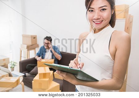 Start up small business entrepreneur SME or freelance woman and man working with box. Young Asian small business owner SME at home office online marketing packaging box and delivery