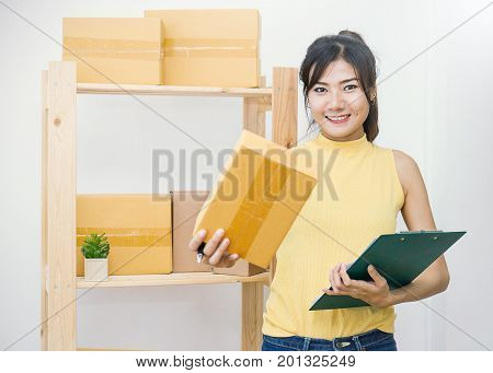 Start up small business entrepreneur SME or freelance woman working with box. Young Asian small business owner SME at home office online marketing packaging box and delivery