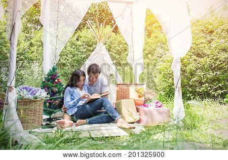A picture of a young couple reading book with a pile of presents in the park celebrate Christmas time hot tropical Christmas