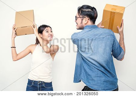 Man and woman fighting with boxes. Young Asian small business owner SME man and woman at home office online marketing packaging and delivery SME concept