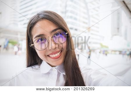 Pretty business woman take a self portrait with her smart phone outdoor Asian nerdy glasses girl selfie with building background