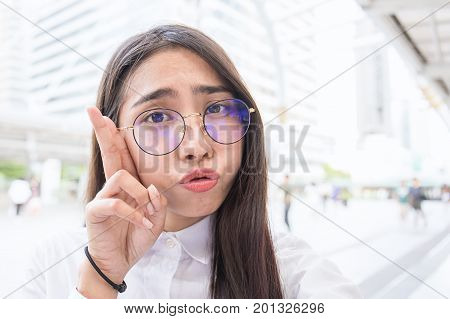 Pretty business woman take a self portrait with her smart phone outside Asian nerdy glasses girl selfie over building background