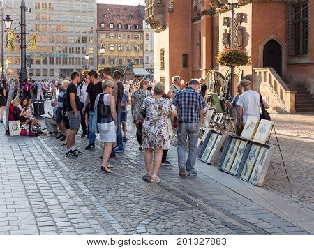 WROCLAW POLAND - AUGUST 15 2017: Painter Selling Pictures At Rynek Market Square In Wroclaw Tourists Looking At The Pictures