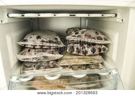 Freezing food in deep freeze, deep-freezing frozen fruit, deep freeze and food