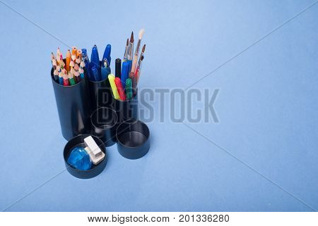Black Holders For Office Supplies With Them On A Blue Background,