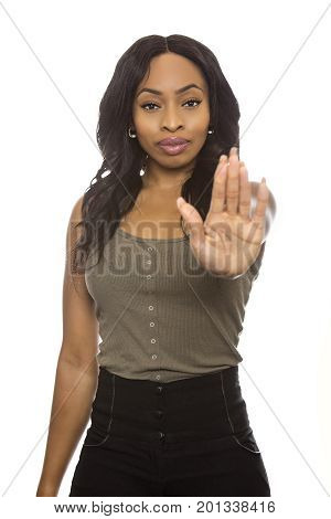 Black female isolated on a white background displaying stop gestures and expressions. She is young and of African American ethnicity.