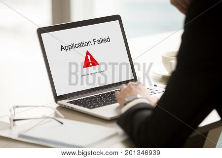 Application failed, businessman having problem with laptop, bad software failure on screen, broken computer stopped working in office, hanging pc caused system crash error message, close up rear view