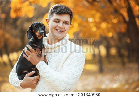 Happy free time with beloved dog! Handsome young man staying in autumn park smiling and holding cute puppy dachshund. Happy pets, friendship, emotions and love concepts.