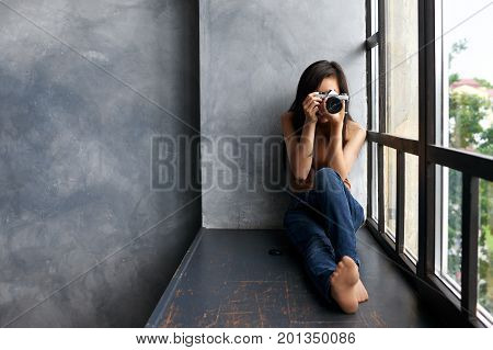 Picture of talented young unrecognizable brunette woman photograpther in jeans holding photo camera taking pictures or making setting sitting barefooted on windowsill by large panoramic window