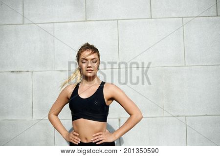 Gorgeous slim young sporty woman with muscular arms and flat abdomen having rest during physical training outdoors with hands on her wasp waist posing at brick wall with copy space for your content